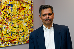 Dr. Pani standing next to his artwork.